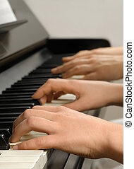 Piano lesson - Four hands playing on the piano keys while...