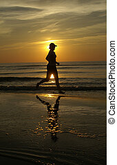 Sunset run - A woman runs barefoot on the beach during the...