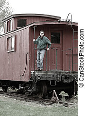 Man On The Train Caboose - Man standing on the back of an...