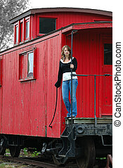 Girl On The Train Caboose standing on the back of an old...