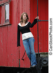 Girl On The Train standing on the back of an old train car...