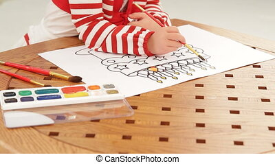 Drawing with brushes - Close up on a little girl drawing a...
