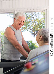 Active senior friends talking and working out in fitness...