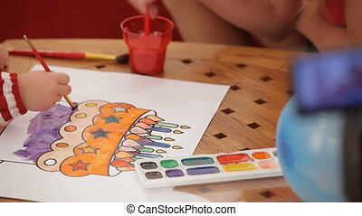 Children coloring an image with watercolors