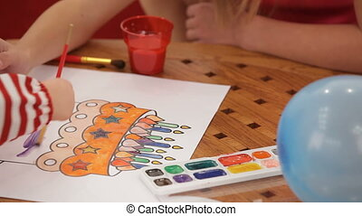 Children drawing a birthday cake with watercolors