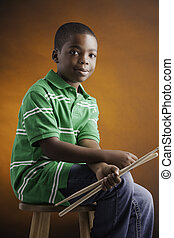 Student and Drum Sticks - A small isolated African American...
