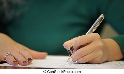 Signing a contract - Close up on womans hands signing a...
