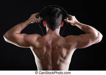 handsome man listening to music on headphone black...