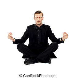 Smart young man in party wear doing yoga. Seated on floor in...