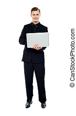 Smiling young man working on laptop against white background