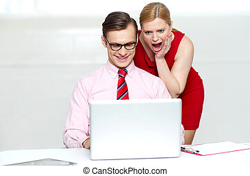 Shocked woman looking into laptop Man working and smiling
