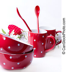 Red polka dot bowls, cups and spoons on a white background