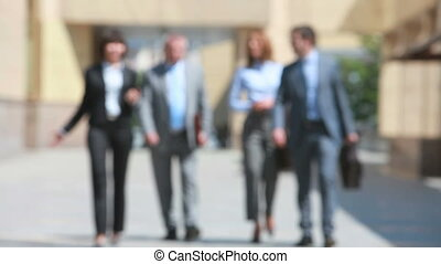 In the background - Elegant business group of four walking...