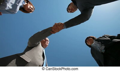Cross handshake - Smiling business teams performing a cross...