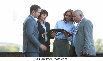 Outdoor discussion - Business team of four holding an...