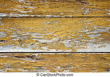 Yellow peeling paint on an old wooden wall