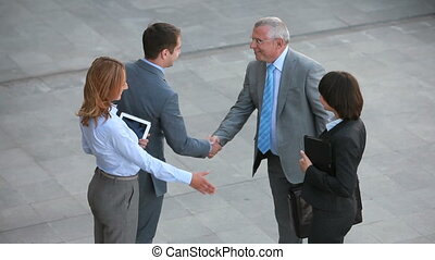 Business bonds - Positive business people shaking hands with...