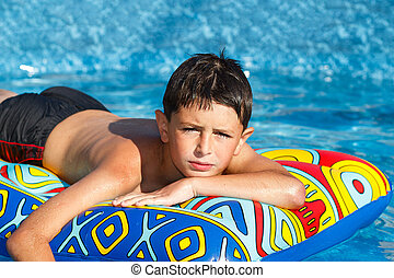 Boy in swimming pool - Boy with inflatable water lounger in...
