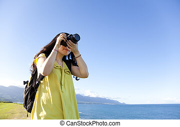 Young woman with backpack standing on the hill taking photo
