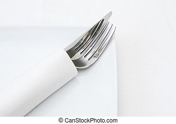 Place setting, knife and fork in white napkin