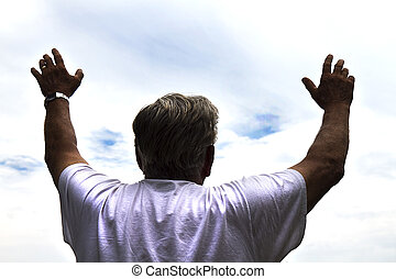 Man Worshiping God - Man with hands raised to the heavens...