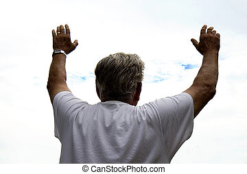Man Praising God - Man with hands raised to the heavens...