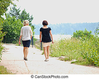Couple of women walking while talking on a gravel road at...