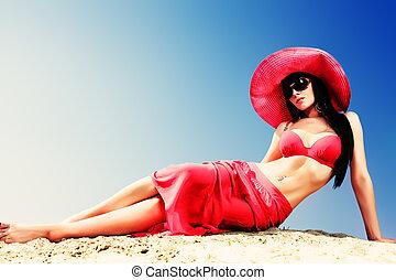 tropics - Beautiful young woman in bikini on a sunny beach.