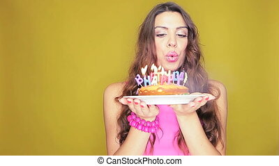 Blowing out the birthday candles - Attractive woman with...