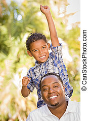 Mixed Race Father and Son Cheering with Fist in Air - Happy...