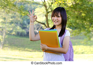 Mixed race ok sign college girl standing at campus
