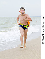 child running on the beach at ocean coast