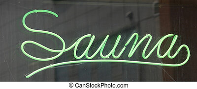 Sauna Sign - A green neon sign in a window that reads Sauna