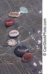 several positive affirmation stones on the shore of the...