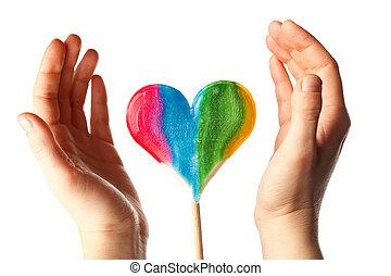hands surrounding lollipop heart