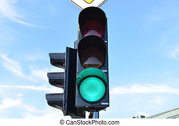 Green color traffic light blue sky in background