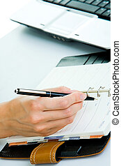 Business planning - Closeup of woman�s hand holding a pen...