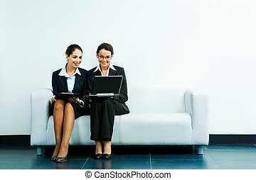 Successful work - Portrait of business ladies sitting next...