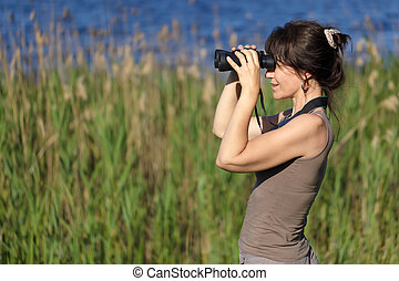 watching wildlife - woman watching wildlife with binoculars...