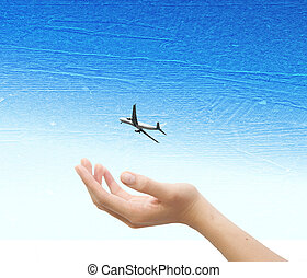 Hand with plane over the blue sky  background