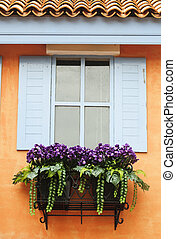 Beautiful window on orange wall decorated with flowers