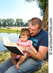Father and little girl reading book