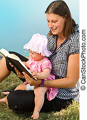 little girl reading book with her mother