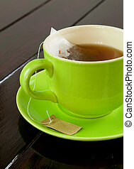 tea cup - green cup of hot tea on wood background