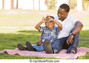 Mixed Race Father and Son Making Heart Hand Sign - Happy...
