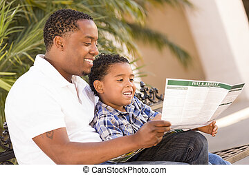 Mixed Race Father and Son Reading Park Brochure Outside -...