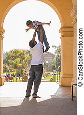 African American Father Lifting Mixed Race Son in the Park -...