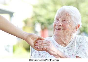 Senior Woman Holding Hands with Caretaker - Happy senior...
