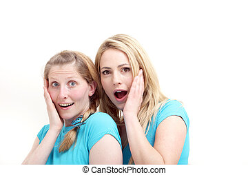Friends reacting in astonishment - Two wide eyed female...