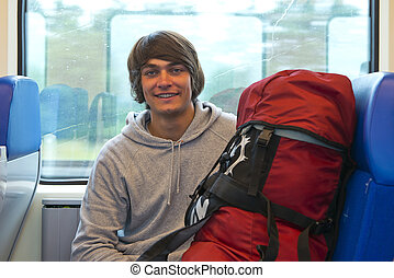 Backpacker smiling into the camera in front of a train...